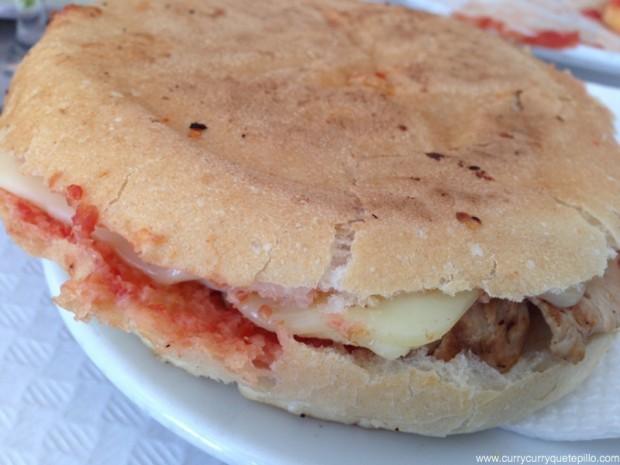 Bocadillo especial de la casa (redonet), con pan untado con tomate y especias y relleno de queso y lomo.